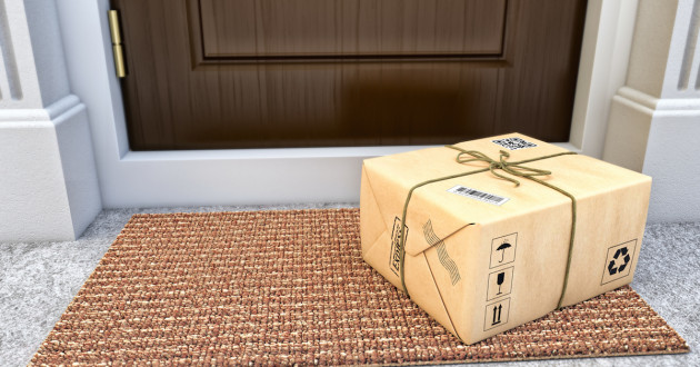 shipping box on mat by the front door
