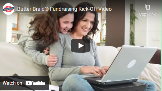 Mom and daughter at a laptop on the couch. Has the play video icon over top